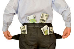 Manngeschäftsmann, der die leeren Taschen sich verstecken hinter Packs des Geldes zeigt Lizenzfreie Stockfotografie