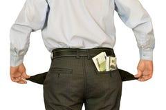 Manngeschäftsmann, der die leeren Taschen sich verstecken hinter Packs des Geldes zeigt Stockfoto
