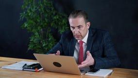 Manngeschäftsmann oder -rechtsanwalt, die bei der Arbeit vor einem Laptop sitzen stock footage