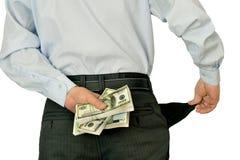 Manngeschäftsmann, der die leeren Taschen sich verstecken hinter Packs des Geldes zeigt Stockfotos