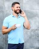 Manngetränkcappuccino sprechen grauen Wandhintergrund des Telefons Selbst wenn Sie den unterwegskaffee trinken, ist jedes Schlück stockbilder