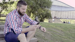 Manngrasen Smartphone, sitzend auf Treppe Schieberschuß, Recht stock footage