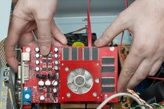 Mannhände baut Videokarte zusammen Stockfotos