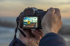 Mannhände, die ein Foto mit DSLR der Sonnenunterganglandschaft machen stockfoto