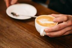 Mannhände, die eine Kappe des Kaffees halten Stockbild