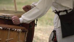 Mannhände, die ledernes Trommelfreien beim Tragen der ländlichen Kleidung spielen Traditionelle Stammes- Trommelleistung stock video