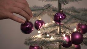 Mannhände, die Spielzeug auf Weihnachtsbaum hängen stock footage