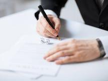 Mannhände mit dem Spielen würfelt unterzeichnenden Vertrag Stockbild