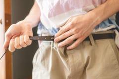 Mannhände setzt an zufällige Hosenhosen oder kurze Hosen und fester Gurtabschluß herauf f stockfoto