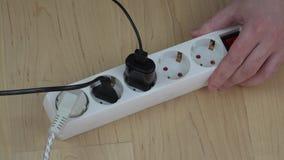 Mannhände stellen Stromerweiterungsschalter ab und trennen Drähte stock footage