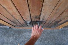 Mannhand auf Garagengriff Öffnet Garagentor Stockfoto