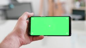 Mannhand, die horizontal den Smartphone mit grünem Schirm an hält stock video