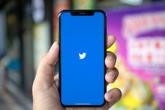 Mannhand, die iPhone X mit Social Networking-Service Twitter hält Stockfotos