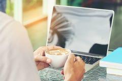 Mannhand, die Schalen Lattekaffee mit Laptopfunktion im cof hält stockfoto