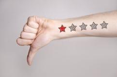 Mannhand, die unten Daumen und eine Sternbewertung zeigt stockfotos