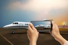 Mannhand machen Foto des Flugzeuges unter Verwendung des Mobiltelefons Stockfotos