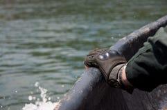 Mannhand mit einem Handschuheinfluß auf Boot Stockbild