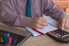 Mannhand unter Verwendung des Taschenrechners und Schreiben lassen Anmerkung mit über Büro der Kosten zu Hause berechnen Der Mann Stockbild
