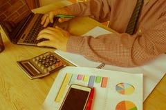 Mannhand unter Verwendung des Taschenrechners und Schreiben lassen Anmerkung mit über Büro der Kosten zu Hause berechnen Der Mann Stockbilder