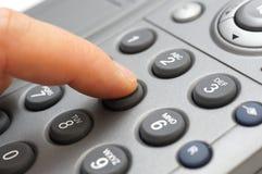 Mannhand wählt eine Telefonnummer Stockfotografie