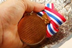 Mannhand, wenn Medaille gehalten wird Lizenzfreies Stockfoto