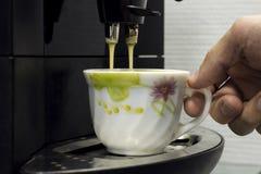 Mannhandgriff ein Schalenkaffee an der Kaffeemaschine Stockfotografie