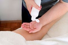 MannHandpumpe aus einer Flasche Massageöl heraus stockfotos