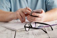 Mannhandtelefon und -taschenrechner im Bürotisch Stockfotografie