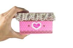 Mannhände, die eine rosa Geschenkbox halten Stockfotografie