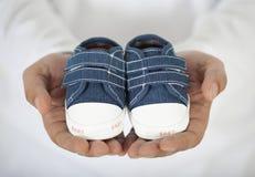 Mannholding-Babyschuhe im Weiß Stockfotos
