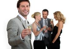 Mannholding-Champagnerglas mit Freunden Stockfotos