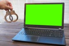 Mannholding fesselt nahe Laptop mit Handschellen stockfoto