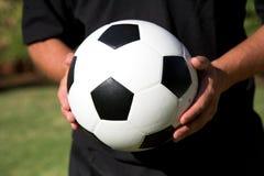 Mannholding-Fußballkugel Lizenzfreie Stockbilder