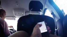 Mannholding iPhone unter Verwendung Uber-App beim Fahren innerhalb des Autos stock video