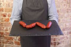 Mannholdingbehälter mit 4 Chorizos an lizenzfreie stockfotos