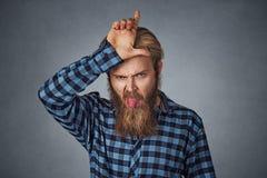 Mannholdingfinger oben an seiner Stirn und heraus an haften Zunge lizenzfreie stockfotografie