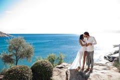 Mannholdingfrau, seine Arme, die um ihre Taille eingewickelt werden und sie halten an zu ihm, Meerblick nahe dem Mittelmeer stockbild