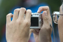 Mannholdingkamera, Fotos machend Stockbild