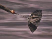 Mannholdingregenschirm im Wind stockbilder