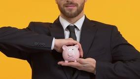 Mannholdingsparschwein auf lokalisiertem Hintergrund, Geldtransaktionen, Ablagerungen stock footage