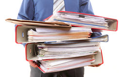 Männlicher Büroangestellter, der einen Stapel Dateien trägt Lizenzfreies Stockfoto