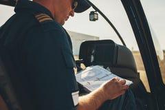 Mannhubschrauberpilot, der eine manuelle Broschüre liest stockfotografie