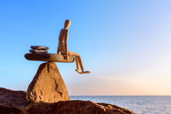Mannikin on the stone. Wooden dummy in balance on the top of stone Royalty Free Stock Image