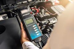 Manninspektionsholding Batterie-Kapazit?ts-Pr?fvorrichtungs-Voltmeter f?r Service-Wartung von industriellem zur Maschinenreparatu stockfoto