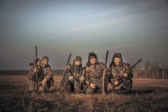 Mannjäger gruppieren Teamporträt auf dem ländlichen Gebiet, das zusammen gegen Sonnenaufganghimmel während der Jagdsaison aufwirf lizenzfreie stockfotos