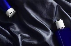 Mannkörpergesundheitswesen-Reisesatz auf dunkelblauem Gewebehintergrund stockbilder