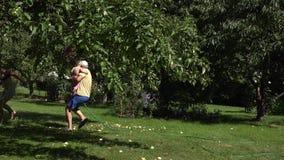 Mannkerlfang und Sprayfrauenmädchen in der Unterwäsche mit Wasser bespritzen im Gartenyard mit einem Schlauch 4K stock video footage