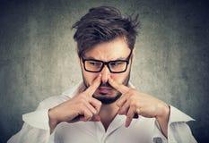 Mannklemmnase mit Fingerblicken mit Ekel etwas stinkt schlechten Geruch lizenzfreies stockbild
