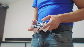 Mannkonzept, das gamepad Handvideokonsole im Lebensstilfernsehen spielt Hand halten den neuen Steuerknüppel, der Videokonsole im  stock video