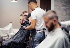 Mannkunden, die haidresser besuchen und Herrenfriseur im Friseursalon lizenzfreie stockbilder